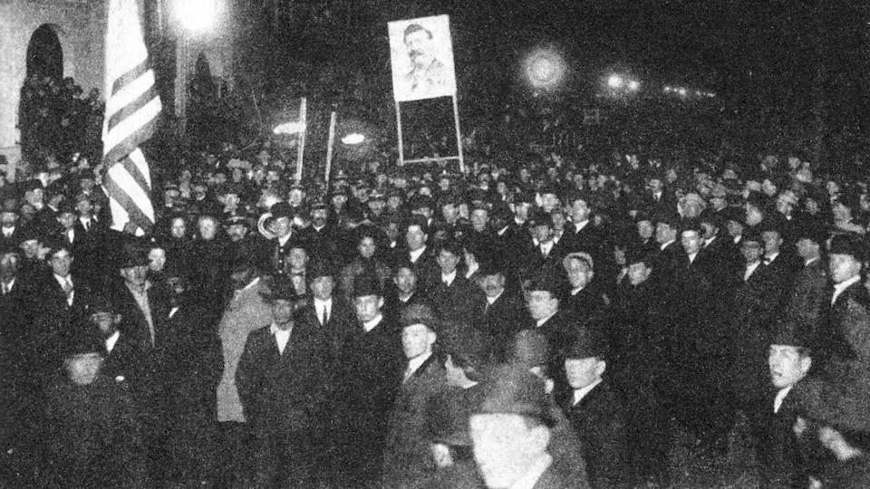 Attroupement d'hommes tenant  drapeaux, flambeaux et pancartes en 1909.