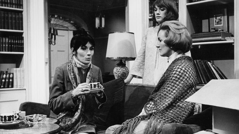Trois femmes discutent dans un petit salon étroit sur cette photo en noir et blanc de la pièce Une maison… un jour, en 1970.