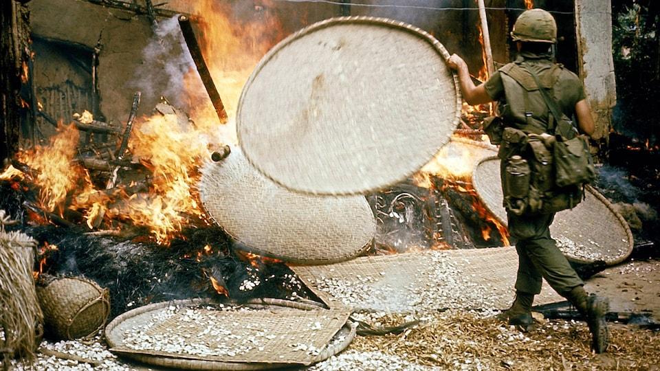 Un soldat lance un panier en osier dans une maison en flamme pendant la guerre du Vietnam.