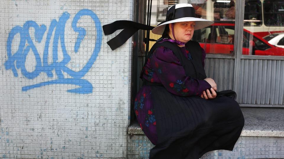 Une mennonite assise devant la vitrine d'un commerce, à côté d'un graffiti bleu illisible, regarde la caméra.