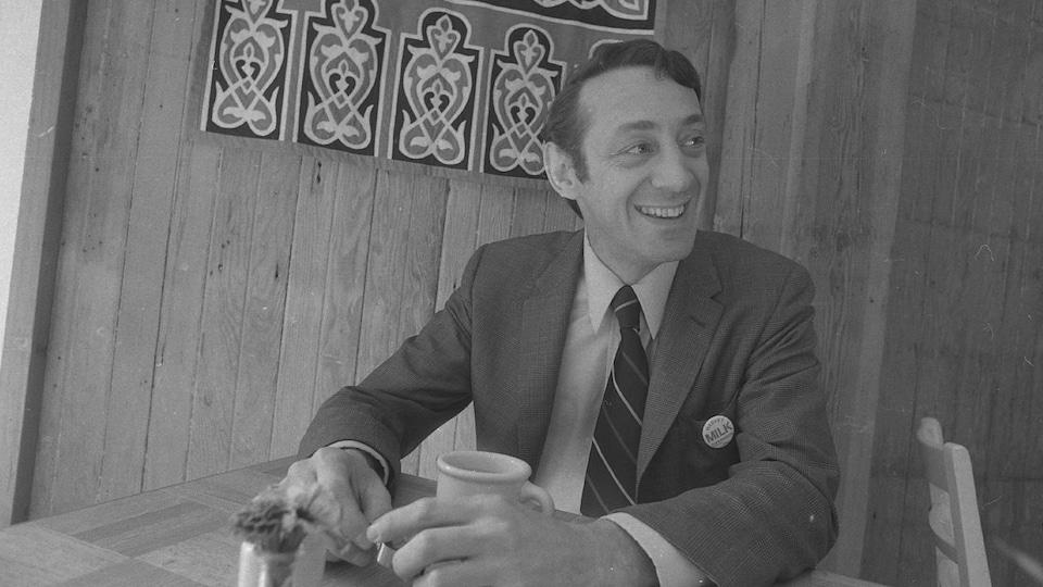 Photo en noir et blanc montrant le militant Harvey Milk souriant, assis à la table d'un restaurant.