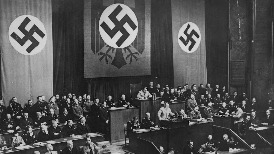 En 1936, le dirigeant nazi Adolf Hitler prononce un discours au Reichstag avec en toile de fond des croix gammées.