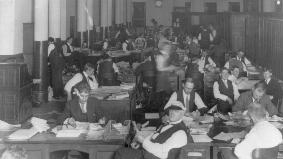 Employés au travail dans la salle de rédaction du journal New York World, vers 1900.