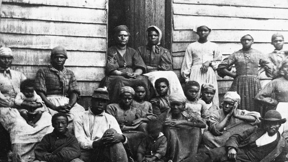 Des anciens esclaves posent devant un refuge temporaire à Arlington, en Virginie, au milieu des années 1860.