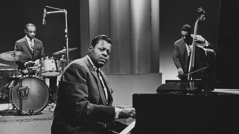 Oscar Peterson au piano avec deux musiciens de son trio en arrière-plan, dans un studio de télévision.