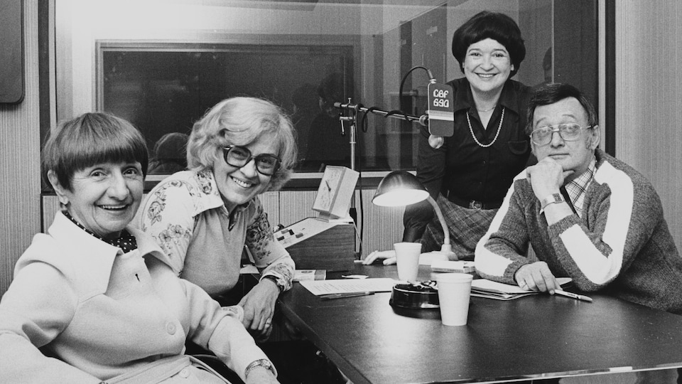 Dans un studio de radio, sont assis autour d'une table, la comédienne Rose Ouellette, l'animatrice Germaine Dugas, la réalisatrice Rita Piché et l'animateur Philippe Laframboise.
