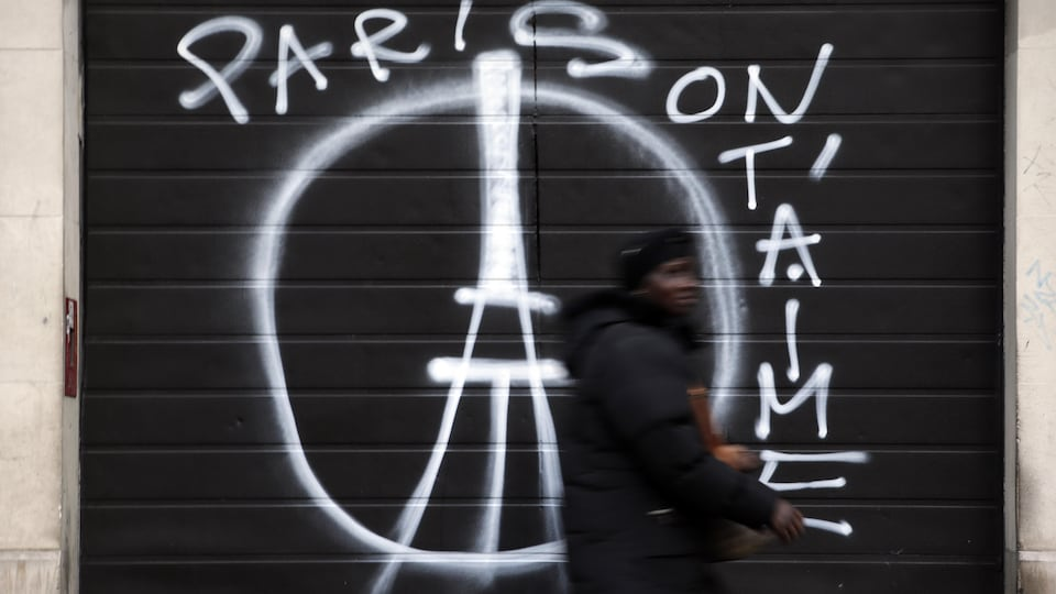 Une femme passe devant un mur où se trouve un graffiti du symbole de la paix avec la tour Eiffel devant.