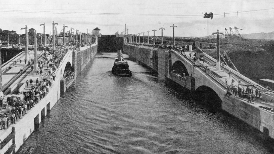 Photo en noir et blanc montrant un bateau à vapeur dans un canal étroit.