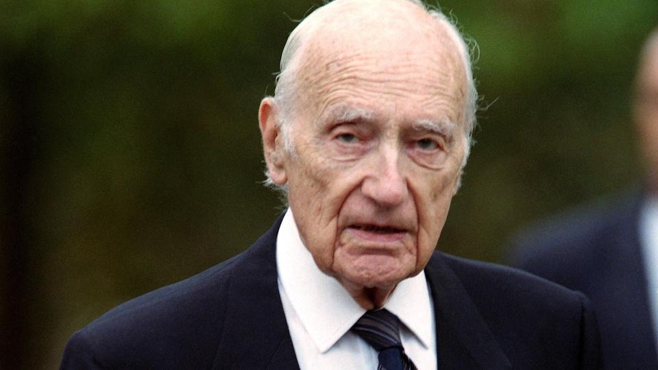 Maurice Papon, vêtu d'un complet, manteau au bras, lors d'une promenade en 1997.