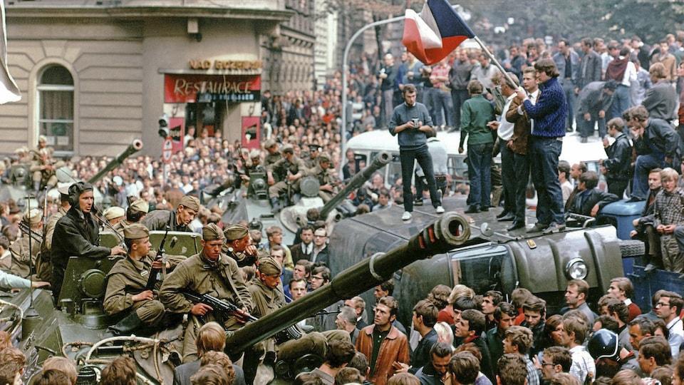 Des Praguois entourent un char d'assaut lors de l'invasion soviétique de la Tchécoslovaquie, en août 1968. Sur un camion renversé, un jeune tient un drapeau tchèque.