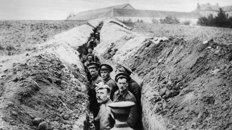 Des soldats britanniques dans une tranchée étroite durant la Première guerre mondiale.
