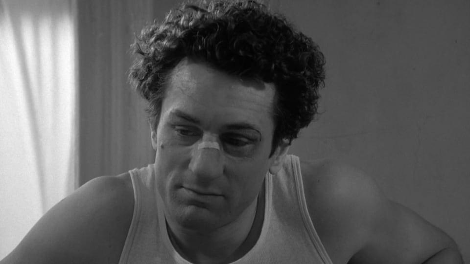 Robert De Niro, pansement sur le nez, regarde vers le sol dans cette image tirée du film Raging Bull, de Martin Scorsese.