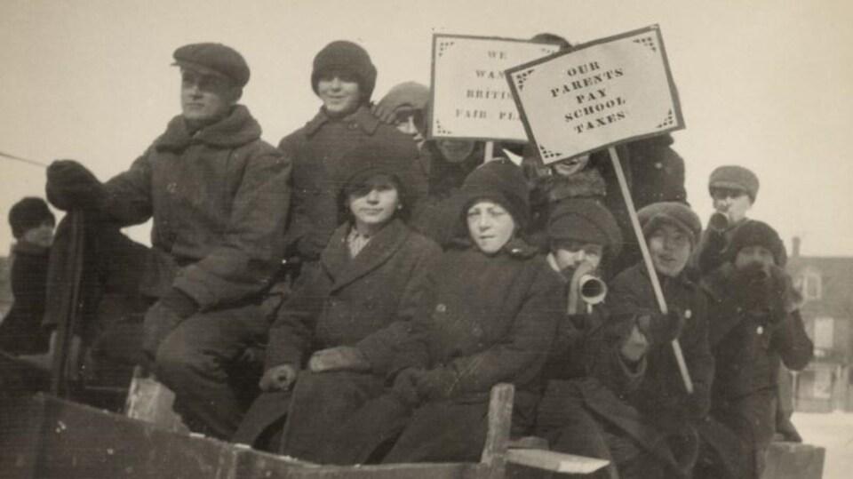 Des écoliers vêtus de manteaux tiennent des pancartes militantes.