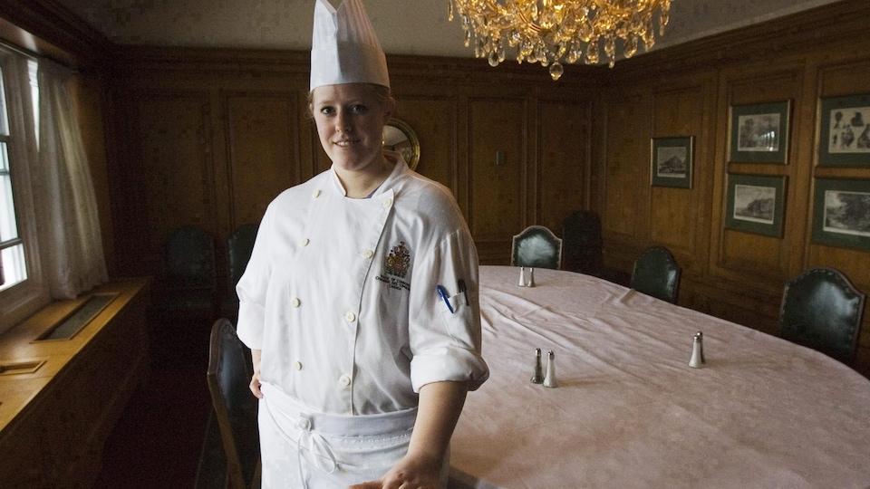 Une cuisinière devant une table de restaurant.