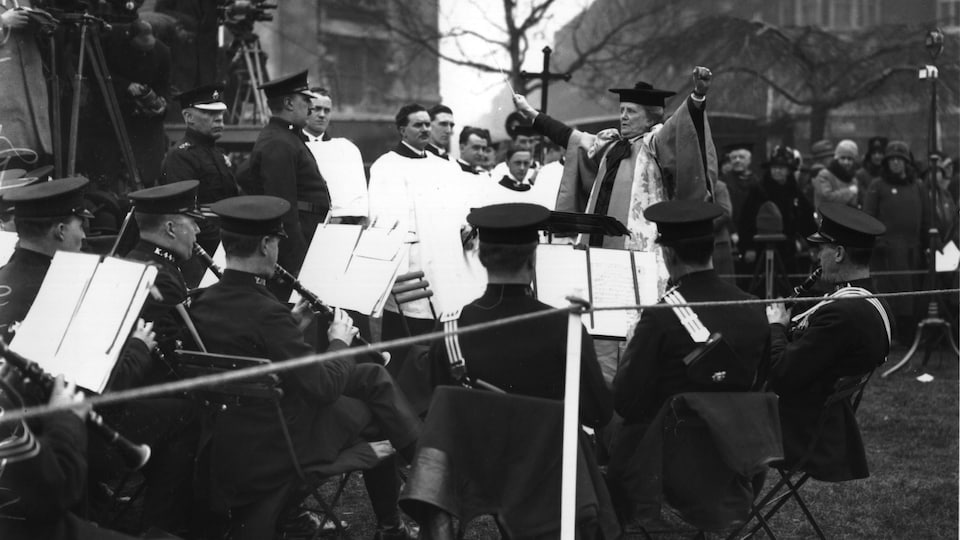 La compositrice Ethel Smyth conduisant un orchestre de policiers lors de dévoilement d'une statue à Londres, en 1930.