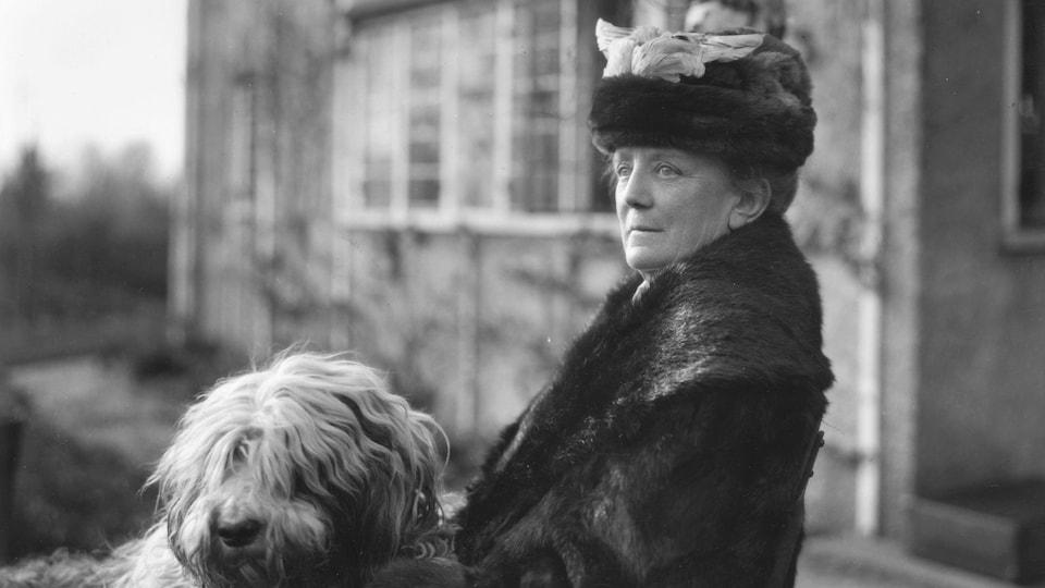 Ethel Smyth devant une maison avec un chien en 1925.