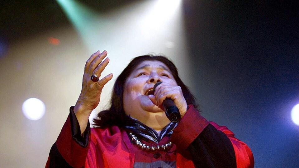 Mercedes Sosa chantant sur scène, le regard et la main tendus vers le ciel.