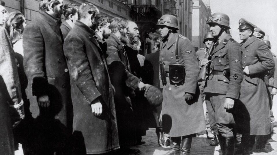 Des SS interrogeant des habitants du ghetto de Varsovie en 1943.