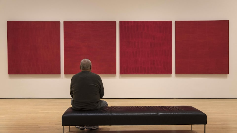 Un homme est assis devant l'œuvre <i>Rouge</i>, de Françoise Sullivan, au Musée d'art contemporain de Montréal.