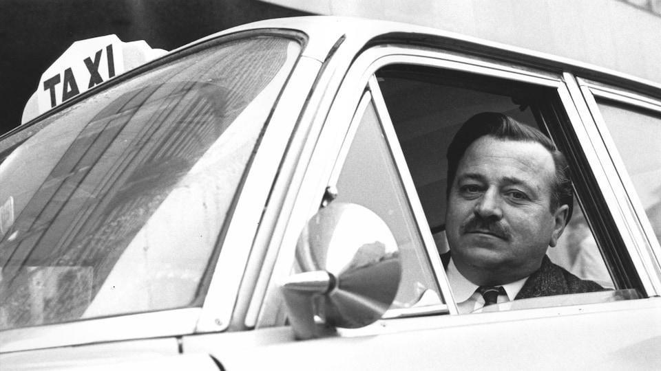 Photo d'archive d'un chauffeur de taxi à bord de son véhicule en 1967.