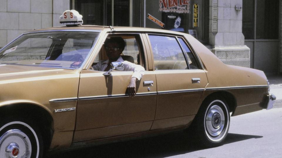 Photo d'archive d'un taxi devant un commerce montréalais en 1982.