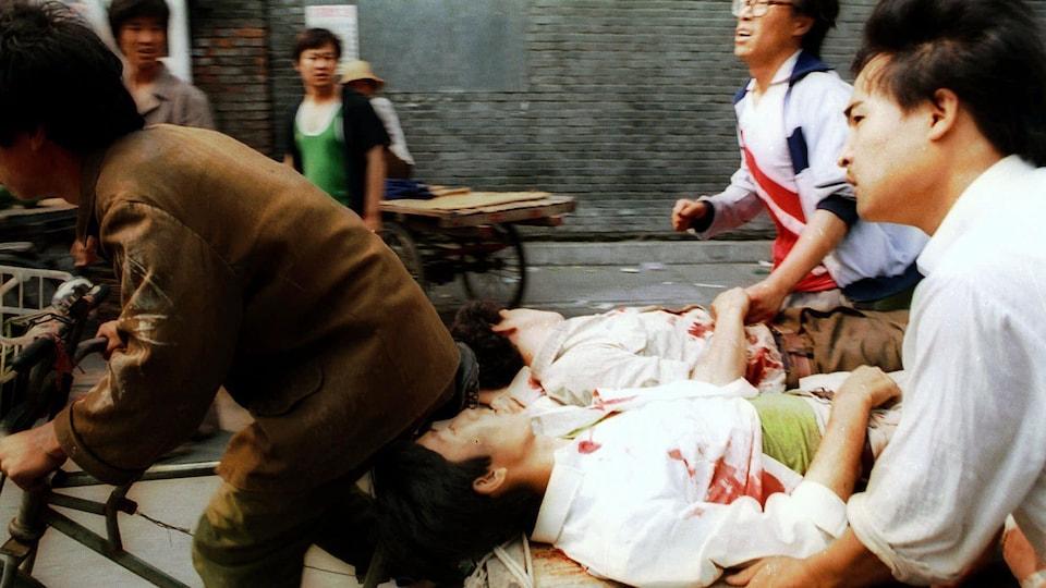 Le 4 juin 1989, deux étudiants blessés sont transportés vers un hôpital après le massacre de la place Tiananmen.