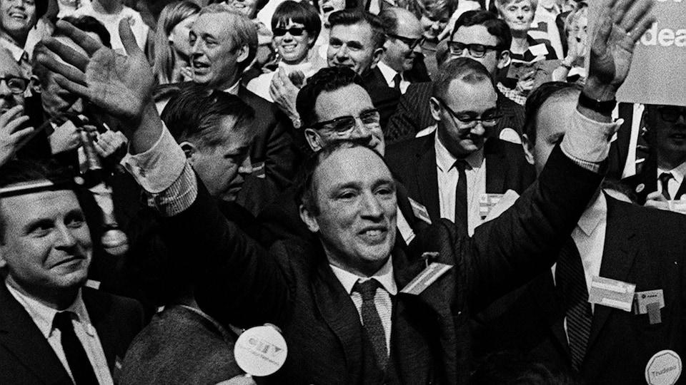 Entouré d'une foule, Pierre Elliott Trudeau lève ses mains en signe de victoire lors de son élection à la tête du Parti libéral, le 7 avril 1968.