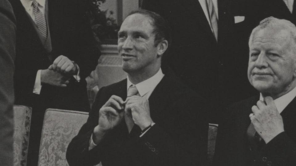 Pierre Elliott Trudeau ajuste sa cravate lors du dévoilement de son premier cabinet, le 6 juillet 1968.
