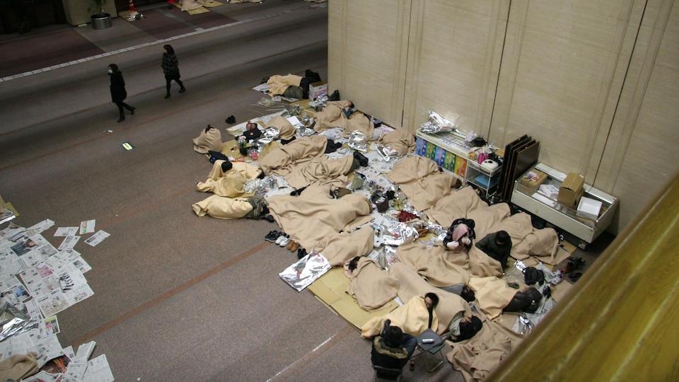 Des Japonais dorment dans un édifice public après avoir été évacués, en mars 2011.