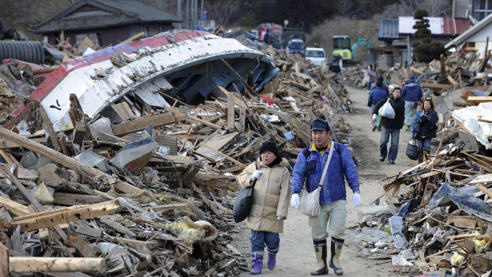 Des résidents de Minamisanriku marchent à travers les décombres laissés par le tsunami du 11 mars 2011.