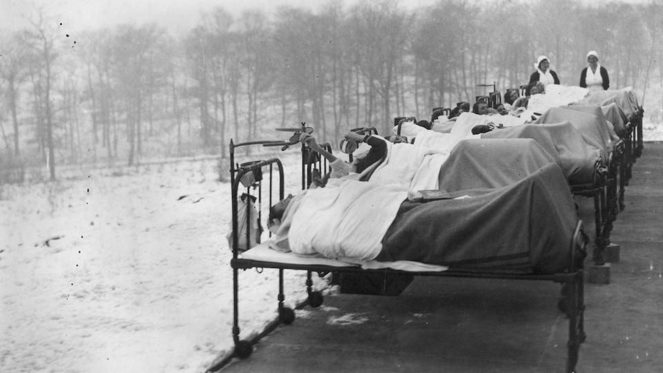 Photo en noir et blanc montrant des patients dans des lits d'hôpital à l'extérieur par une température hivernale.