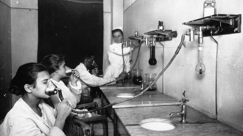 Photo en noir et blanc montrant des patients atteints de tuberculose utilisant des inhalateurs.