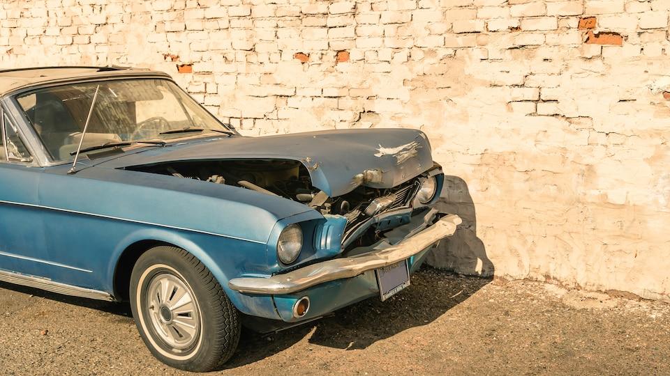 Une voiture des années 1970 accidentée devant un mur de briques