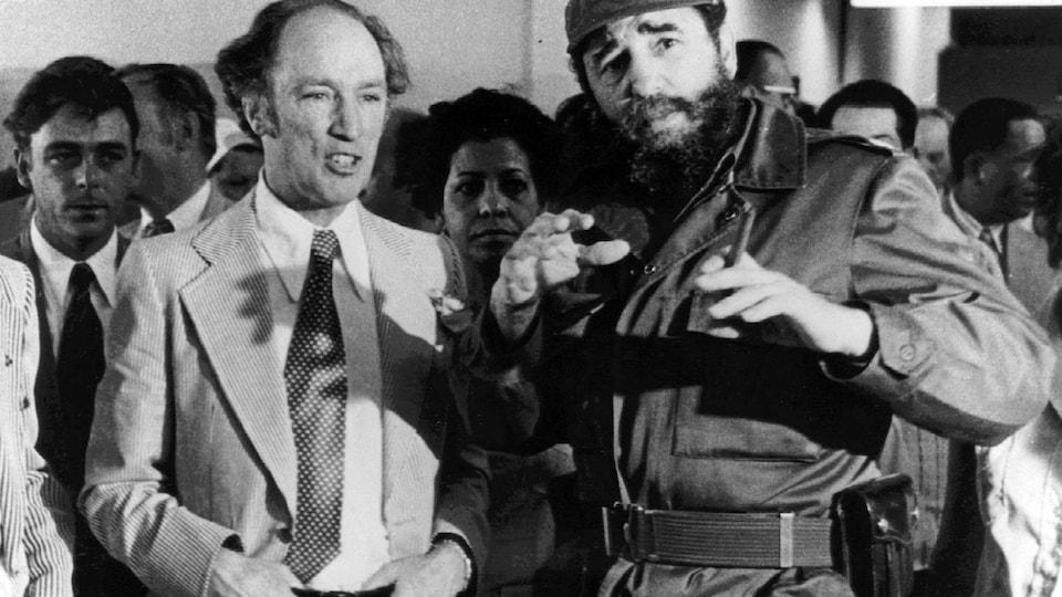 Photo en noir et blanc de deux dirigeants en plein discussion devant une poignée de Cubains