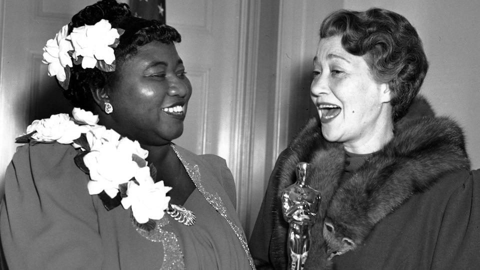 Deux femmes en tenue de soirée s'échangent un Oscar en 1940.