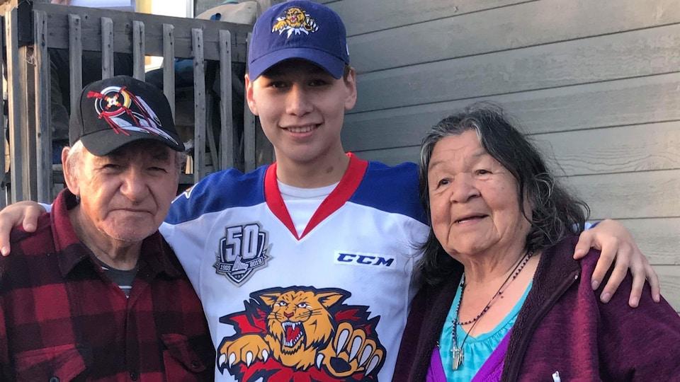Un jeune Attikamekw portant un chandail de hockey accompagné d'un Attikamekw et d'une Attikamekw plus âgés.