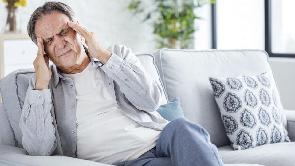 Assis sur un divan, un homme se touche les tempes en raison d'un mal de tête.