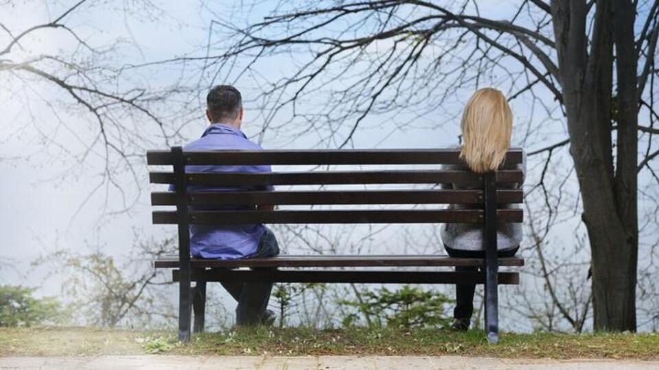Un couple éloigné sur un même banc.