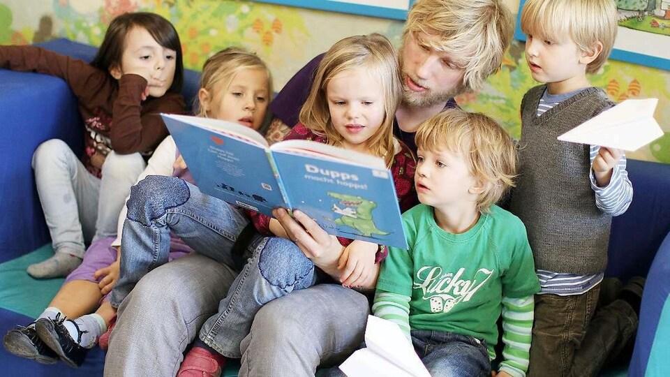 Un homme lit une histoire à des enfants dans un centre de la petite enfance.