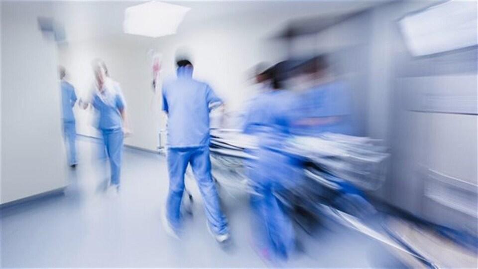Une civière en mouvement avec du personnel médical dans un couloir d'hôpital.