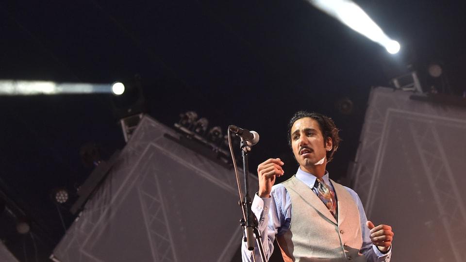 Il chante en tailleur beige sur une scène.