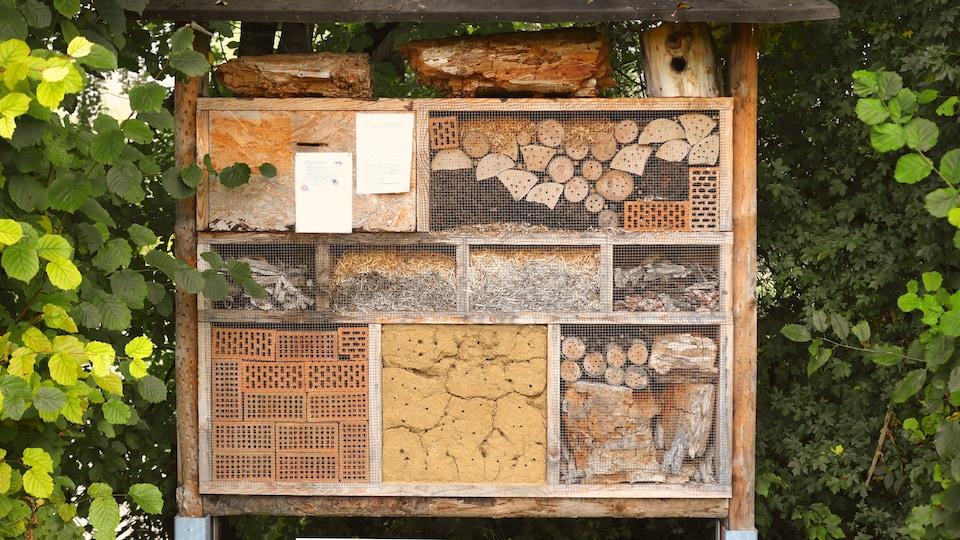 Une structure en bois non traité est compartimentée, de sorte à créer une maison pour les insectes dans le but de préserver la biodiversité. Les compartiments de grandeurs différentes sont remplis de différentes matières : paille, pommes de pins, brindilles, branches d'arbres, brique, pot en terre cuite et feuilles mortes.