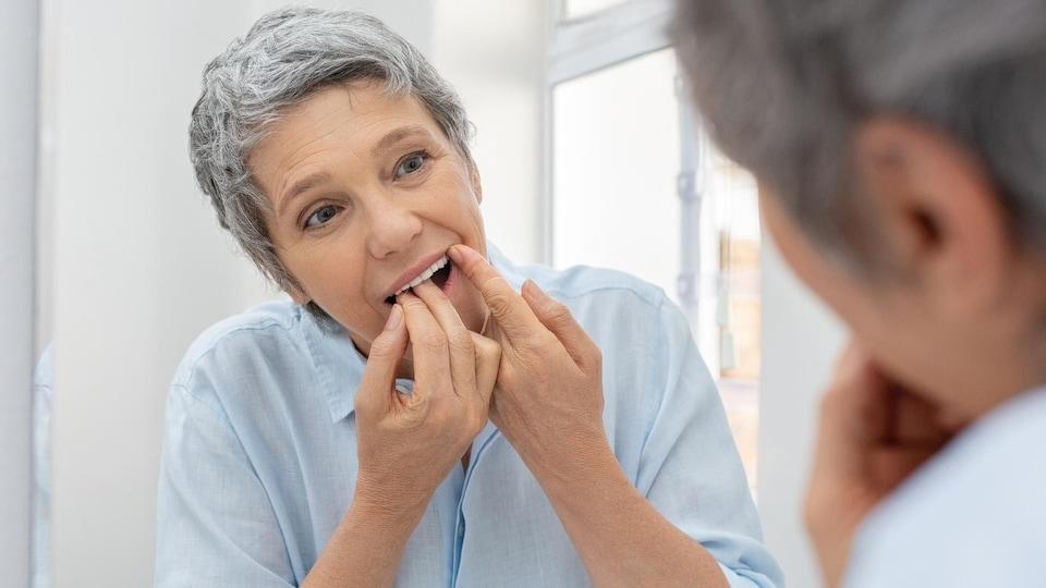 Une femme âgée se passe la soie dentaire devant un miroir.