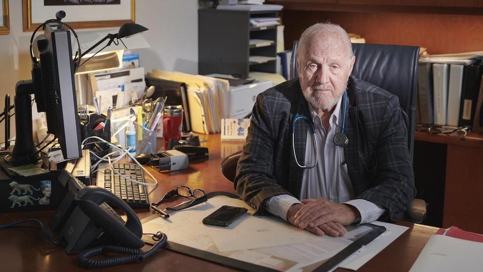 Il est assis à son bureau.