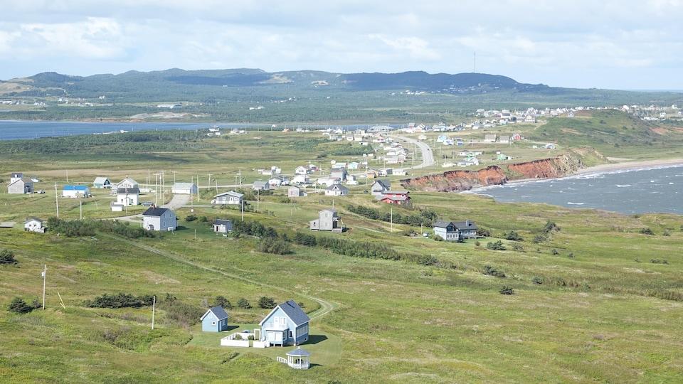 Vue sur des maisons et la mer, avec les collines de Bassin à l'arrière.