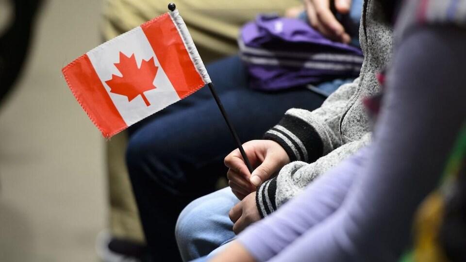 Une personne tient un petit drapeau du Canada.