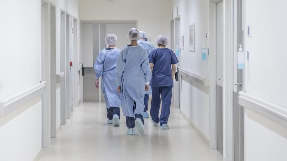 Quatre employés médicaux marchent de dos dans un couloir d'hôpital.