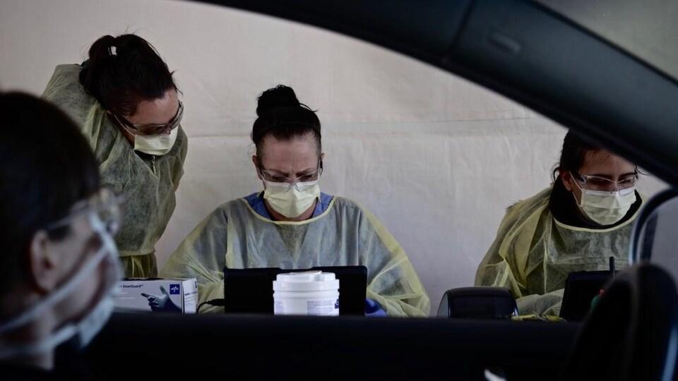 Des infirmières en blouse en train de travailler.