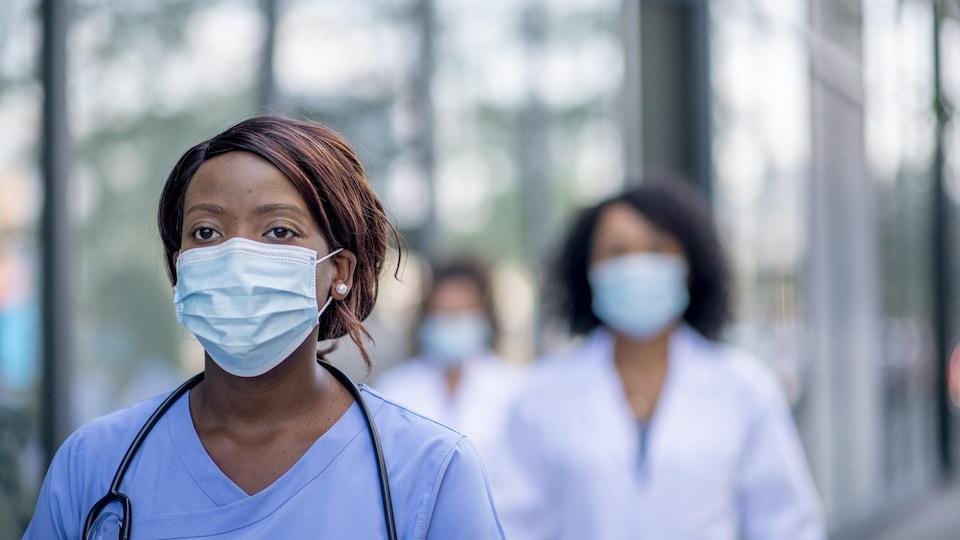Une infirmière masquée marche à l'extérieur le long d'un établissement de santé, suivi par deux collègues.