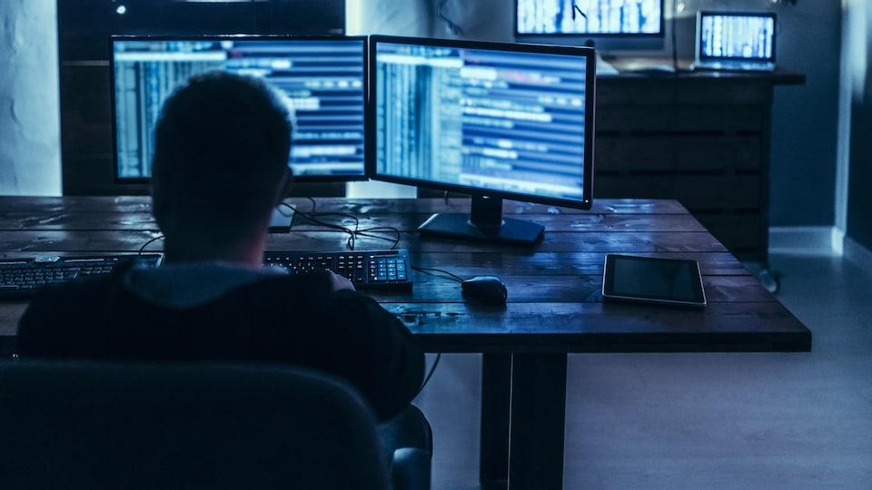 Un homme tape sur un clavier devant deux écrans d'ordinateurs.